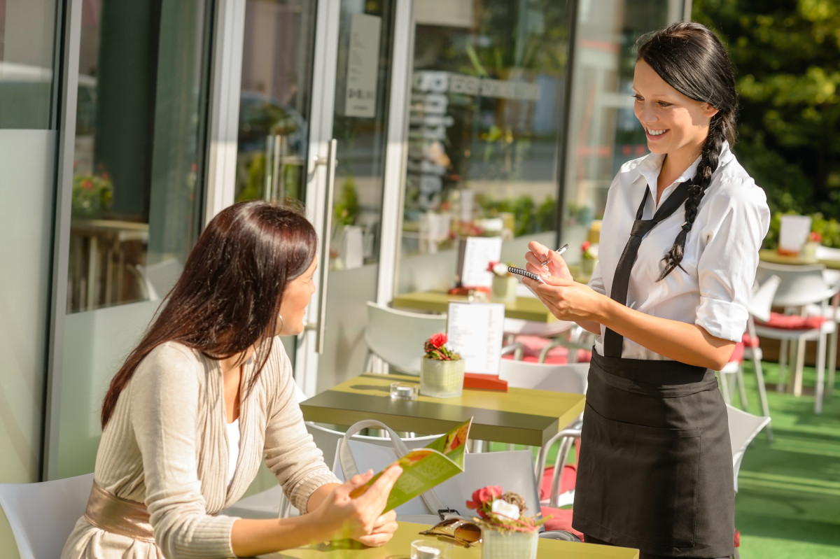 Waitress taking woman's order at cafe bar menu smiling sunny